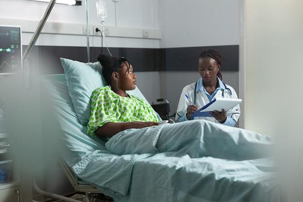 Afro-amerikaanse jonge volwassene met ziekte in gesprek met dokter