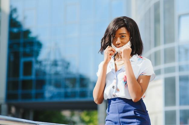 Afro-amerikaanse jonge vrouw die gezichtsmasker buitenshuis draagt.