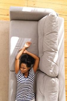 Afro-amerikaanse jonge vrouw draagt gestripte t-shirt rusten, slapen op de bank met armen omhoog thuis