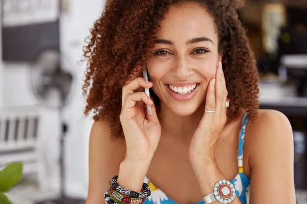 Afro-amerikaanse jonge vrouw met vrolijke uitdrukking, stralende warme glimlach heeft telefoongesprek