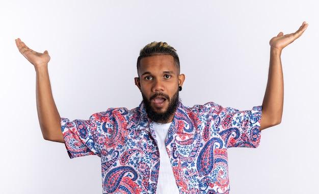 Afro-amerikaanse jongeman in een kleurrijk shirt die er verward en gefrustreerd uitziet en zijn armen opsteekt die over wit staan