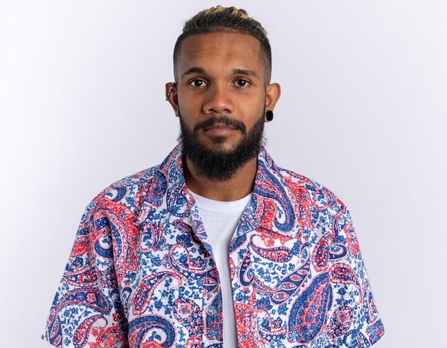 Afro-amerikaanse jongeman in een kleurrijk shirt die naar de camera kijkt met een serieuze zelfverzekerde uitdrukking op een witte achtergrond