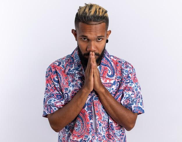 Afro-amerikaanse jongeman in een kleurrijk shirt handpalmen bij elkaar houdend als biddend over wit