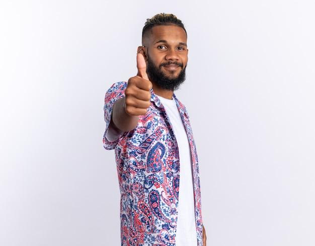 Afro-amerikaanse jongeman in een kleurrijk shirt kijkend naar de camera die vrolijk lacht en duimen opsteekt terwijl hij over wit staat