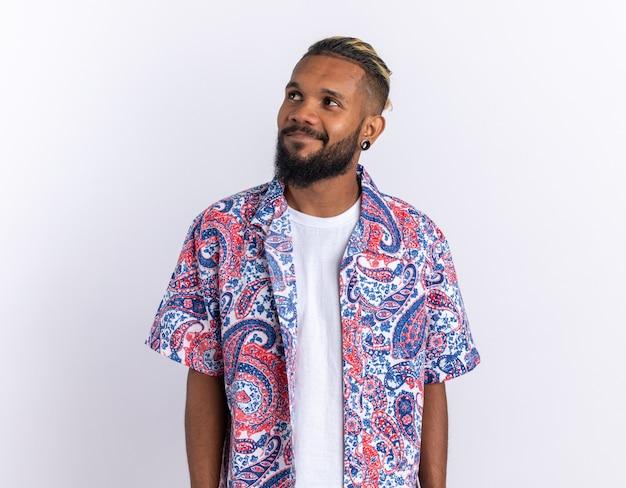 Afro-amerikaanse jongeman in een kleurrijk shirt opzij kijkend glimlachend vrolijk gelukkig en positief over wit