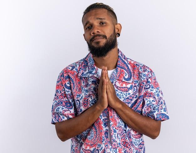 Afro-amerikaanse jongeman in kleurrijk shirt kijkend naar camera met hoopsuitdrukking die handpalmen bij elkaar houdt