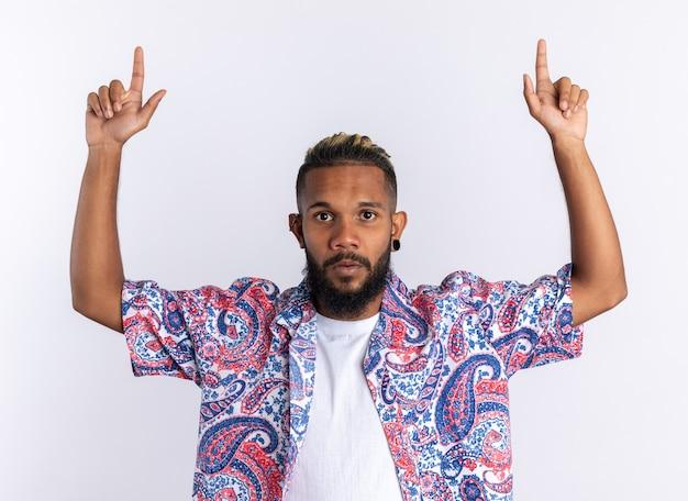 Afro-amerikaanse jongeman in kleurrijk shirt kijkend naar camera verrast wijzend met wijsvingers omhoog staand op witte achtergrond
