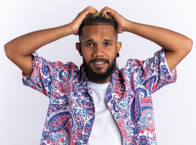 Afro-amerikaanse jongeman in kleurrijk shirt kijkend naar camera verward met handen op zijn hoofd