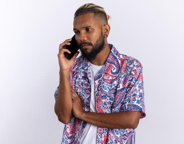 Afro-amerikaanse jongeman in kleurrijk shirt verdrietig en verward tijdens het praten op mobiele telefoon