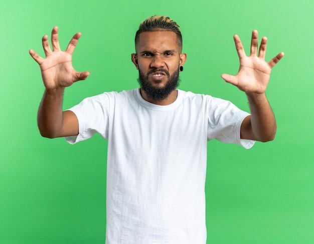 Afro-amerikaanse jongeman in wit t-shirt beangstigend kijkend naar camera die klauwen gebaar maakt als een kat a