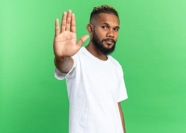 Afro-amerikaanse jongeman in wit t-shirt die naar camera kijkt met een serieus gezicht dat een stopgebaar maakt met de hand die over een groene achtergrond staat