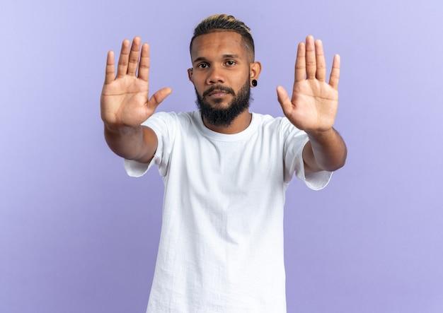 Afro-amerikaanse jongeman in wit t-shirt die naar camera kijkt met een serieus gezicht dat een stopgebaar maakt