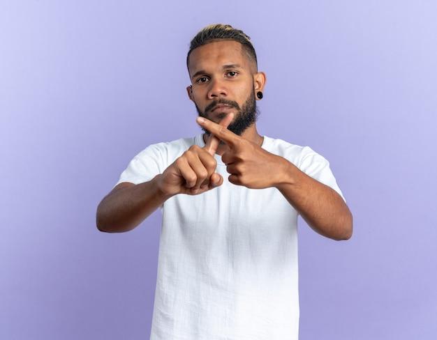 Afro-amerikaanse jongeman in wit t-shirt die naar camera kijkt met een serieus gezicht dat een verdedigingsgebaar maakt en wijsvingers kruist die over een blauwe achtergrond staan