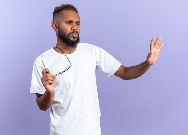 Afro-amerikaanse jongeman in wit t-shirt die ontevreden opzij kijkt