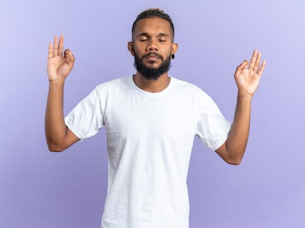 Afro-amerikaanse jongeman in wit t-shirt die probeert te ontspannen en meditatiegebaar maakt met vingers met gesloten ogen