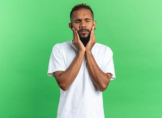 Afro-amerikaanse jongeman in wit t-shirt die verward en ontevreden over zijn handen kijkt