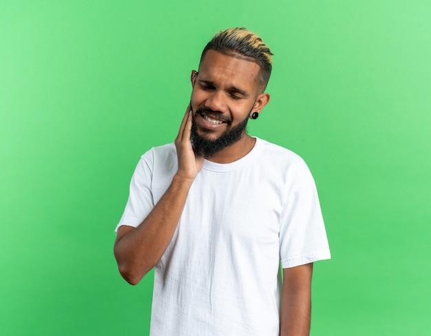 Afro-amerikaanse jongeman in wit t-shirt die verward kijkt met zijn hand op zijn gezicht