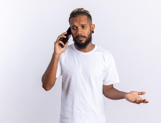Afro-amerikaanse jongeman in wit t-shirt die verward kijkt terwijl hij op een mobiele telefoon praat die over een witte achtergrond staat