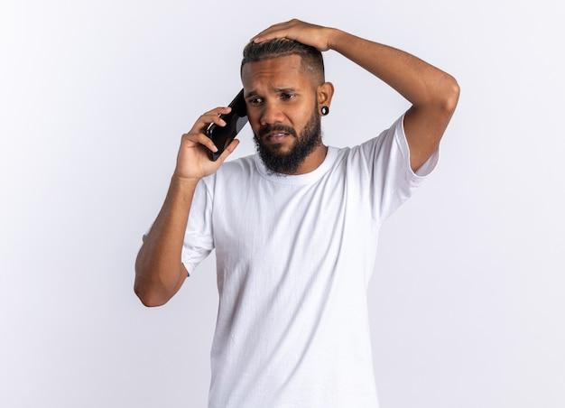 Afro-amerikaanse jongeman in wit t-shirt die verward kijkt terwijl hij op een mobiele telefoon praat die over wit staat