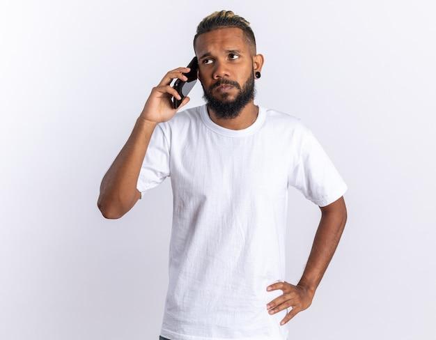 Afro-amerikaanse jongeman in wit t-shirt die verward kijkt terwijl hij op mobiele telefoon praat