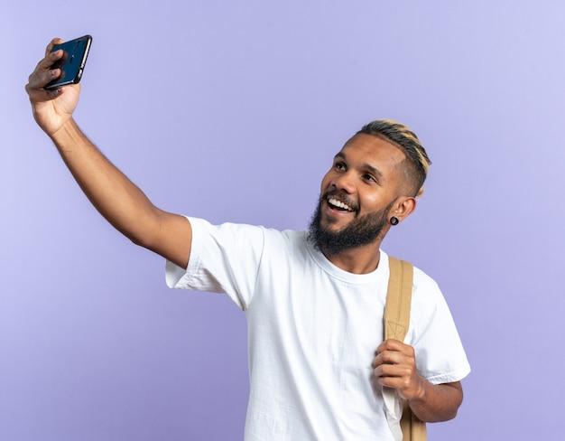 Afro-amerikaanse jongeman in wit t-shirt doet selfie met smartphone happy