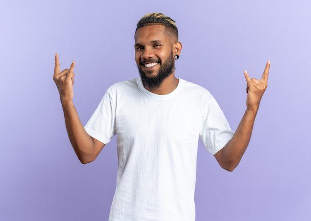 Afro-amerikaanse jongeman in wit t-shirt kijkend naar camera, blij en vrolijk lachend met rotssymbool rock