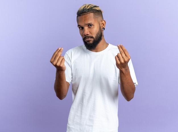 Afro-amerikaanse jongeman in wit t-shirt kijkend naar camera die geldgebaar maakt en vingers wrijft over blauwe achtergrond