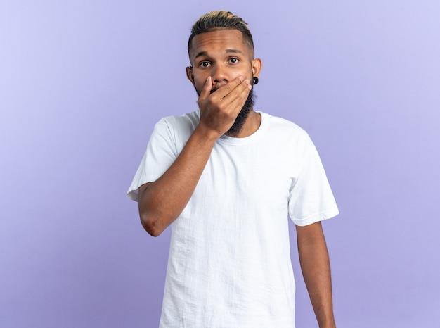 Afro-amerikaanse jongeman in wit t-shirt kijkend naar camera die geschokt is en mond bedekt met hand?