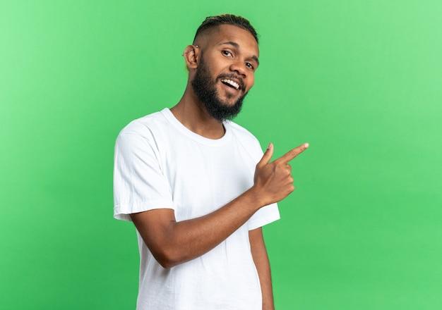 Afro-amerikaanse jongeman in wit t-shirt kijkend naar camera glimlachend vrolijk wijzend met wijsvinger naar de zijkant