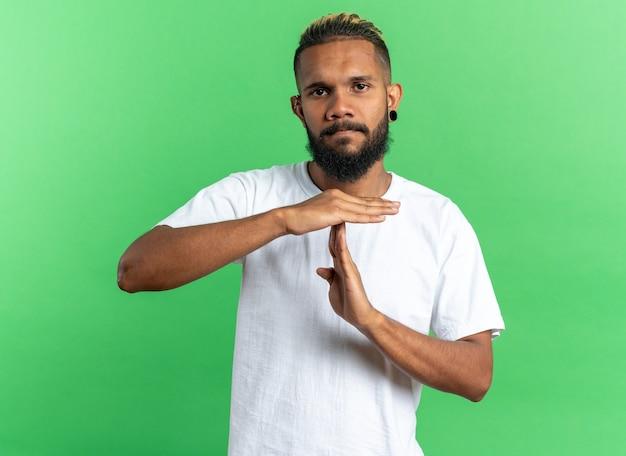 Afro-amerikaanse jongeman in wit t-shirt kijkend naar camera met serieus gezicht en maakt time-outgebaar met handen over groene achtergrond