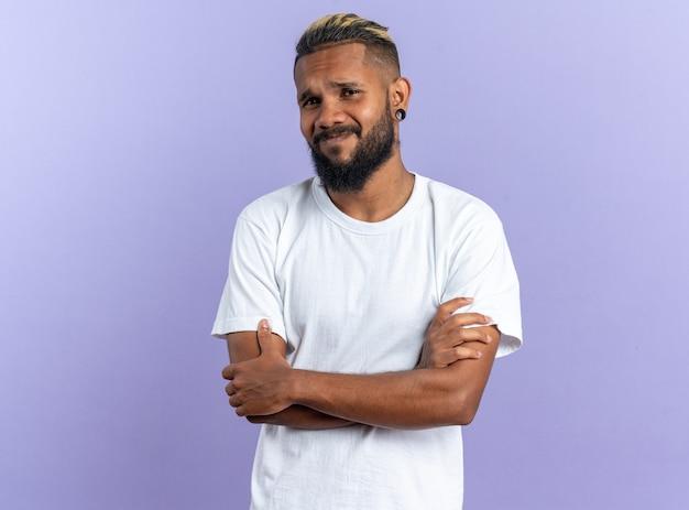 Afro-amerikaanse jongeman in wit t-shirt kijkend naar camera verward met gekruiste armen