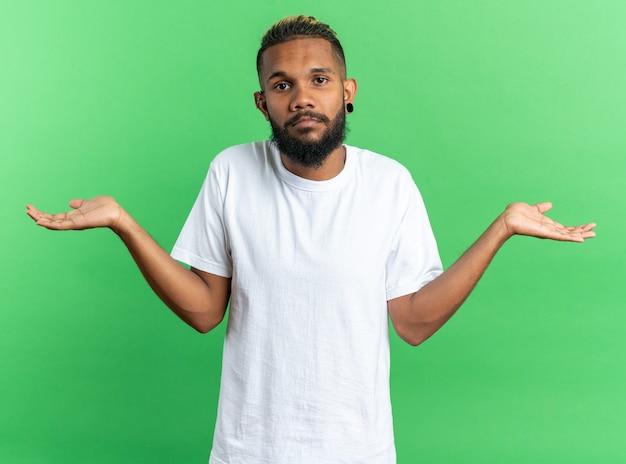 Afro-amerikaanse jongeman in wit t-shirt kijkend naar camera verward spreidende armen naar de zijkanten twijfelend over groene achtergrond