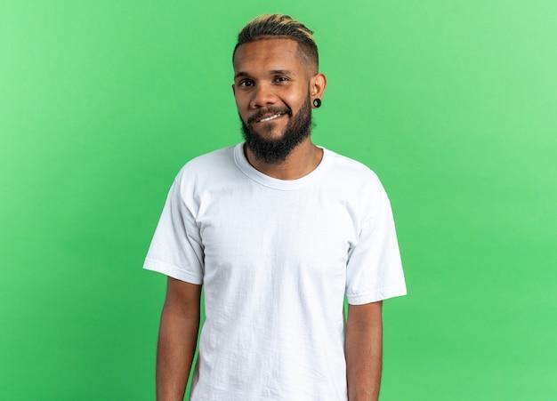 Afro-amerikaanse jongeman in wit t-shirt kijkt naar de camera met een glimlach op het gezicht gelukkig