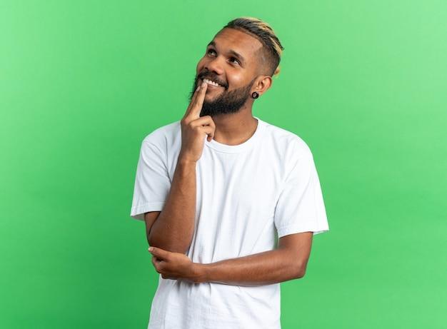 Afro-amerikaanse jongeman in wit t-shirt kijkt verbaasd glimlachend op terwijl hij over groen staat