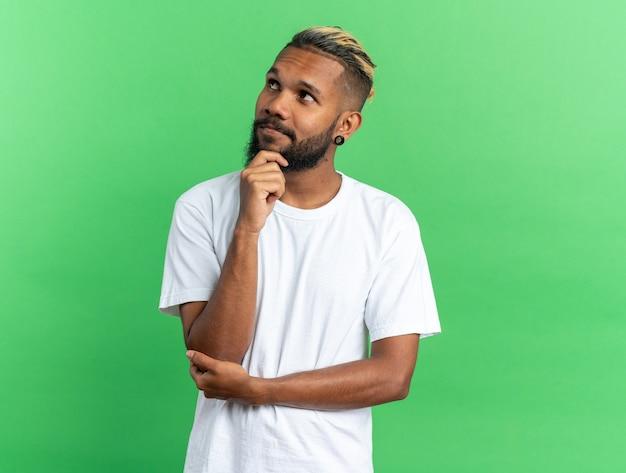 Afro-amerikaanse jongeman in wit t-shirt kijkt verbaasd op met de hand op zijn kin die over groene achtergrond staat