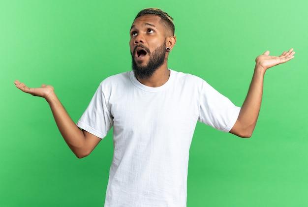 Afro-amerikaanse jongeman in wit t-shirt kijkt verward op en spreidt armen naar de zijkanten over groene achtergrond