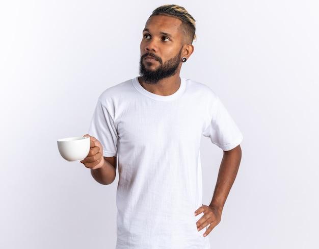 Afro-amerikaanse jongeman in wit t-shirt met kopje thee opzij kijkend met een serieus gezicht over wit