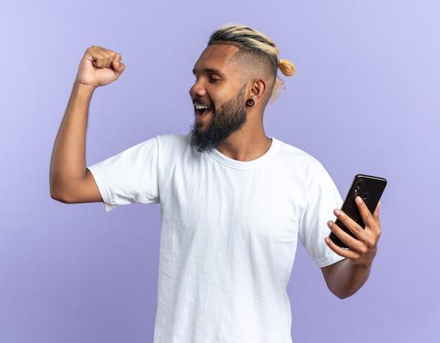 Afro-amerikaanse jongeman in wit t-shirt met smartphone balde vuist blij en opgewonden schreeuwend over zijn succes