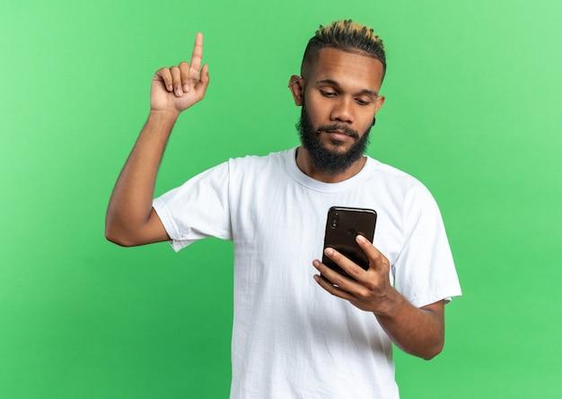 Afro-amerikaanse jongeman in wit t-shirt met smartphone die ernaar kijkt en wijsvinger toont met nieuw idee over groene achtergrond