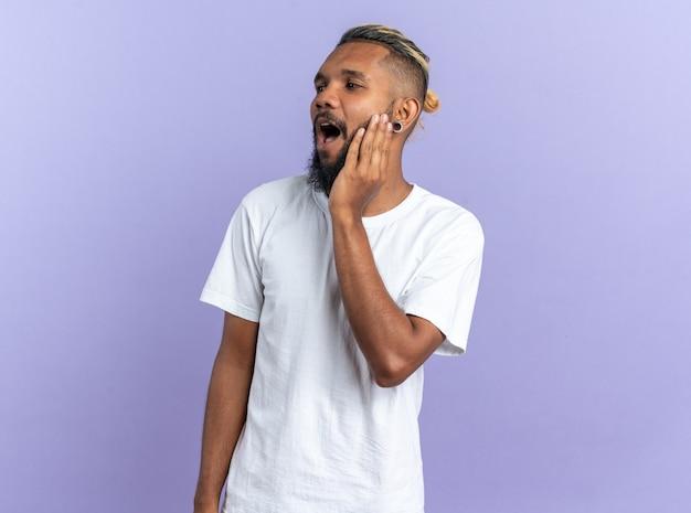 Afro-amerikaanse jongeman in wit t-shirt opzij kijkend verbaasd en verrast terwijl hij over blauw staat