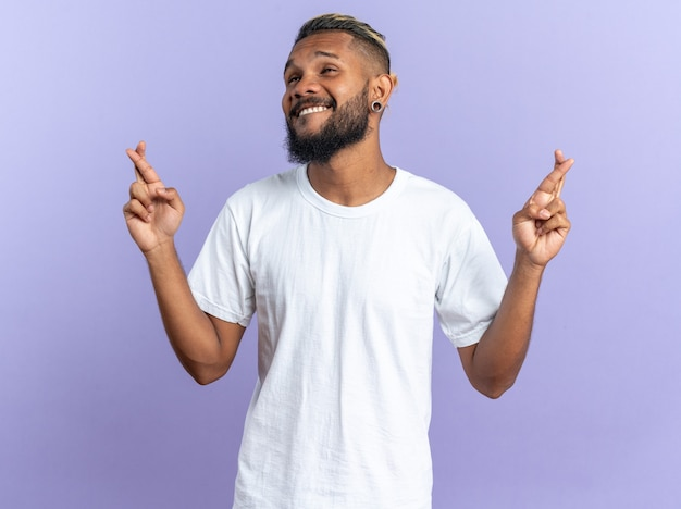 Afro-amerikaanse jongeman in wit t-shirt vrolijk en vrolijk probeert te ontspannen en maakt meditatiegebaar met vingers