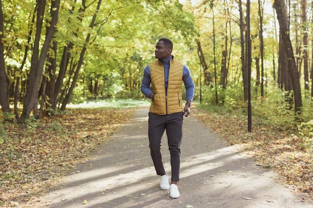 Afro-amerikaanse jongeman wandelingen in herfst park op warme zonnige dag