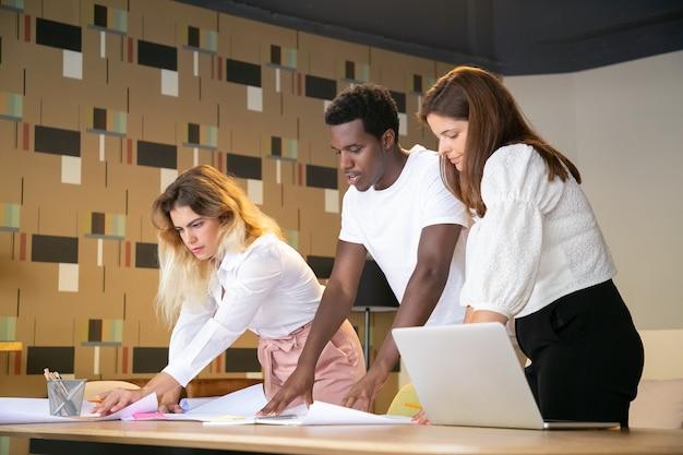 Afro-amerikaanse jongen en blanke vrouwen die aan design werken