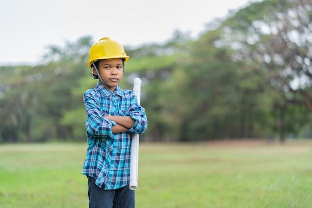 Afro-amerikaanse jongen in ingenieur har blauwdrukken te houden