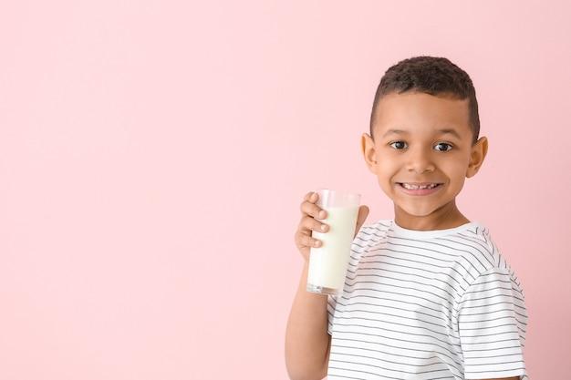 Afro-amerikaanse jongen met melk op roze