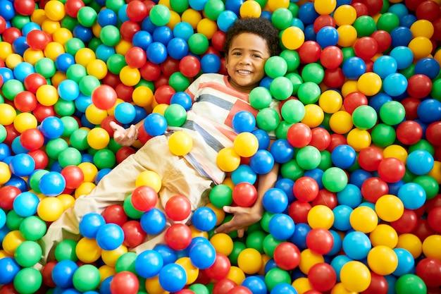 Afro-amerikaanse jongen spelen in ballpit