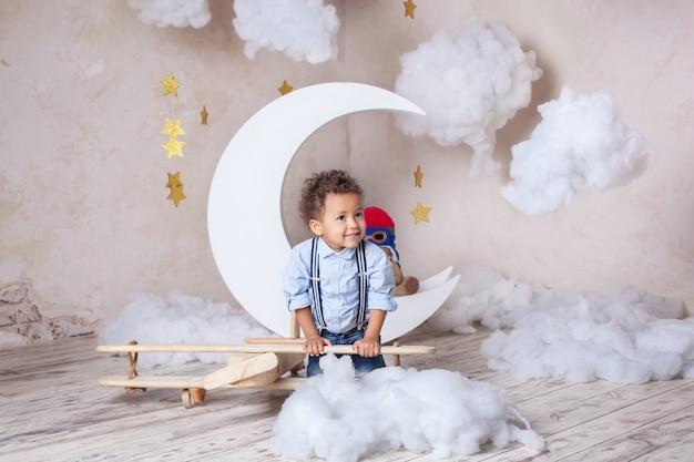 Afro-amerikaanse jongetje. de zwarte jongen. school, voorschools onderwijs. droom, carrière. een kleine jongen speelt met een houten vliegtuig speelgoed. kindertijd, verbeelding. kind speelt eco speelgoed in de kleuterschool