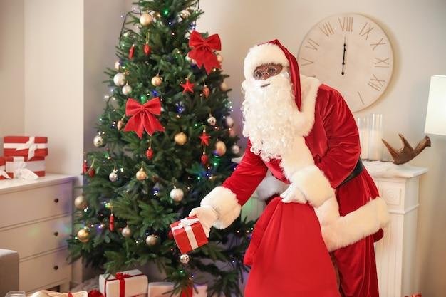 Afro-amerikaanse kerstman die geschenken onder de kerstboom in de kamer legt
