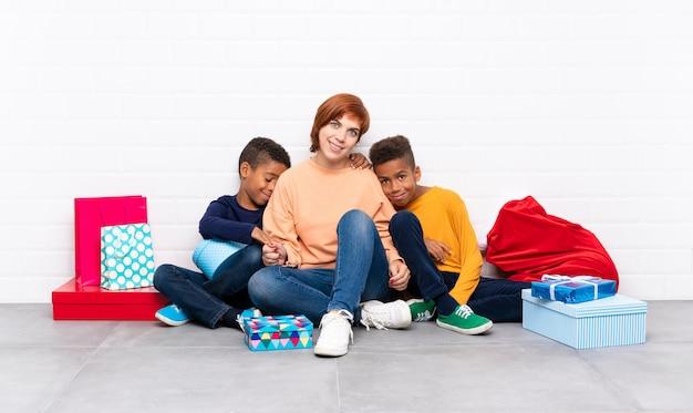 Afro-amerikaanse kinderen met hun moeder onder vele geschenken voor kerstvakantie