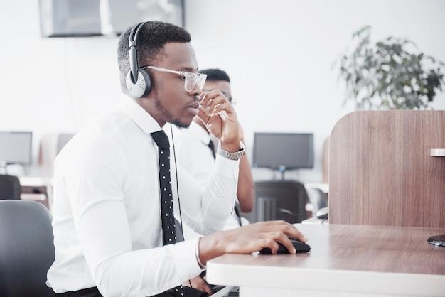 Afro-amerikaanse klantenondersteuning operator met handsfree headset werken op kantoor